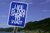 Life is Too Short To Wait sign with a beach on background