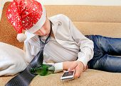 stock photo of untidiness  - Sad and Tired Teenager in Santa Hat with Bottle of the Beer and Cellphone on the Sofa - JPG
