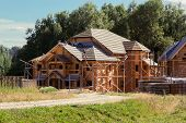 stock photo of chalet  - builders cover the roof of a log house - JPG