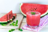 pic of mints  - Glass of fresh watermelon juice with mint leaves and sliced fruit on wooden table - JPG