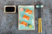 image of masago  - Sushi rolls with masago served on turquoise plate with pickled ginger soy sauce and chopsticks - JPG