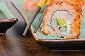 picture of masago  - Closeup California maki sushi with masago on the table - JPG