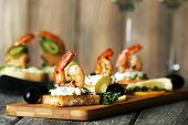 foto of canapes  - Appetizer canape with shrimp and olives on cutting board on table close up - JPG