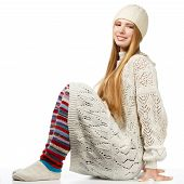 stock photo of knitted cap  - Young beautiful smiling woman with long blonde hair siting in white knitted sweater cap and striped gaiters isolated on white background - JPG