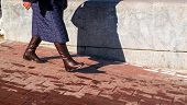 foto of kilt  - A woman walks on pavement with brown boots and blue kilt dress - JPG