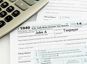 foto of irs  - USA tax form 1040 for year 2014 with a pen and calculator illustrating completion of tax forms for the IRS - JPG