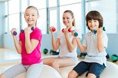 image of physical education  - Cheerful mother and two children exercising with dumbbells in health club while sitting on the fitness balls together - JPG