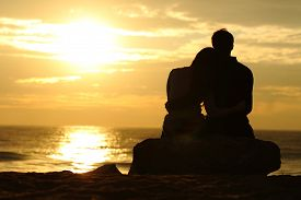 stock photo of cuddle  - Couple silhouette cuddling and watching sun at sunset on the beach - JPG