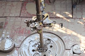 picture of tong  - Drill pipe and rig tong on the rig floor while making up for drilling with dirty water based mud - JPG