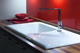 stock photo of tapping  - Modern Stylish Kitchen with Wooden Counter White Enamel Sink and Modern Silver Faucet Tap - JPG