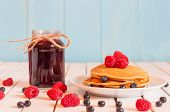 stock photo of mason  - Stack of wheat golden pancakes or pancake cake with freshly picked raspberry on a dessert plate - JPG