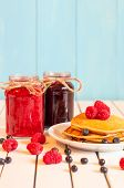 stock photo of picking tray  - Stack of wheat golden pancakes or pancake cake with freshly picked raspberries on a dessert plate - JPG