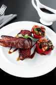 picture of braai  - fresh red beef meat steak barbecue garnished vegetable salad and basil on white plate over black wooden table with bbq sauce in sauceboat - JPG