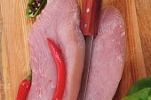 stock photo of turkey dinner  - fresh raw turkey steak fillet with red hot chili pepper and green salad on cutting board over wooden table - JPG