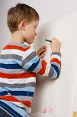 picture of little boys only  - Little boy drawing with pencil white paper on easel - JPG