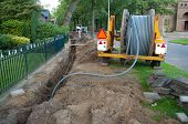 stock photo of urbanisation  - building side where they put fiberglass cables into the ground for faster internet - JPG