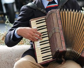 stock photo of accordion  - Accordion being played accordionist on his knee - JPG