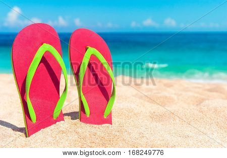 Beautiful beach. Beach sandals on the sandy coast. Summer holiday and vacation concept. Tropical beach.