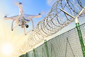 Drone monitoring barbed wire fence on state border or restricted area. Modern technology for securit poster