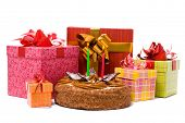 Pie with two candles and gifts in boxes on a white background