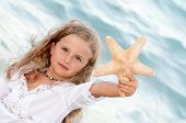 Happy summer vacation - beautiful girl with starfish at the beach