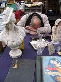 picture of bric-a-brac  - Sleeping salesman at his stand at a fleemarket - JPG