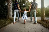 Happy Stylish Parents Holding Hands With Daughter And Walking In Sunny Summer Street, Tender Family poster