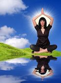 Sexy brunette girl sitting in lotus pose on a riverside - conceptual image