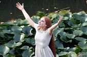 Young happy woman in long dress rises hands to heaven - outdoor