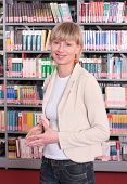 Portrait of a young blond woman inside a book store