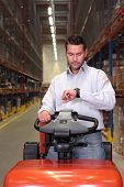 A warehouse worker on a vehicle checking his watch.