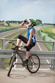 Mountain biker drinking isotonic drink and having rest over highway