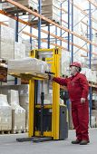 Senior,experienced worker in red uniform with bar code reader working in warehouse