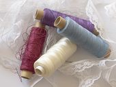 colored bobbins in the white lace