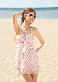 Young beautiful woman in summer dress and sunglasses on the beach