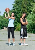 Young fitness couple of man and woman playing basketball outdoors