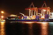 Armazém portuário com cargas e contentores à noite