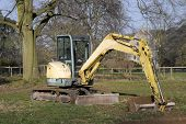 picture of jcb  - digger in countryside digging holes in the ground - JPG
