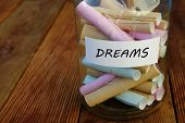 Jar With The Word Dreams Written On Paper And Attached On It. A Jar With Rolled Papers poster