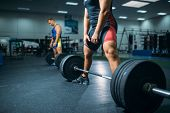 Two weightlifters doing exercise with barbells poster