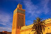 Ornate Minaret Rises Above Mosque Walls Into Blue Sky In Morocco