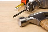 picture of hammer drill  - hammer and tape measure on wood brick - JPG