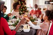 Multi generation mixed race family sitting at Christmas dinner table holding hands and saying grace, poster