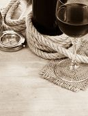 glass of red wine and bottle on wood background