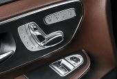 Door Handle With Power Seat Control Buttons Of A Luxury Passenger Car. Brown Leather Interior With W poster