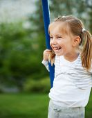 image of seesaw  - Pretty little girl on outdoor seesaw - JPG