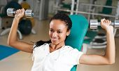 picture of weight-lifting  - A young woman lifting free weights with a confident smile - JPG