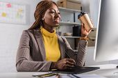 Smiling Adult African American Adult Businesswoman Sitting At Computer Desk, Drinking Coffee And Usi poster
