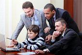 Kid boy explains multi ethnic business team how to work