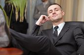 image of table manners  - businessman relaxing at the office with his shoes on the desk - JPG